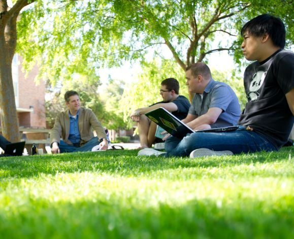 students sitting on lawn with professor
