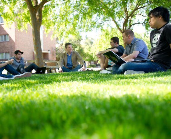 students sitting on campus lawn with professor
